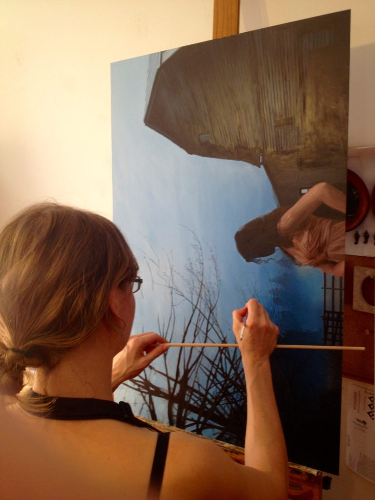 artist Rebecca Luncan working in the studio on figurative oil painting