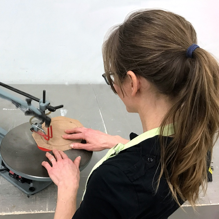Artist Rebecca Luncan cutting a liner for a custom frame on a scroll saw