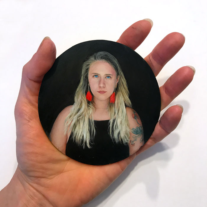 Artist Rebecca Luncan holding her miniature portrait painitng of young woman